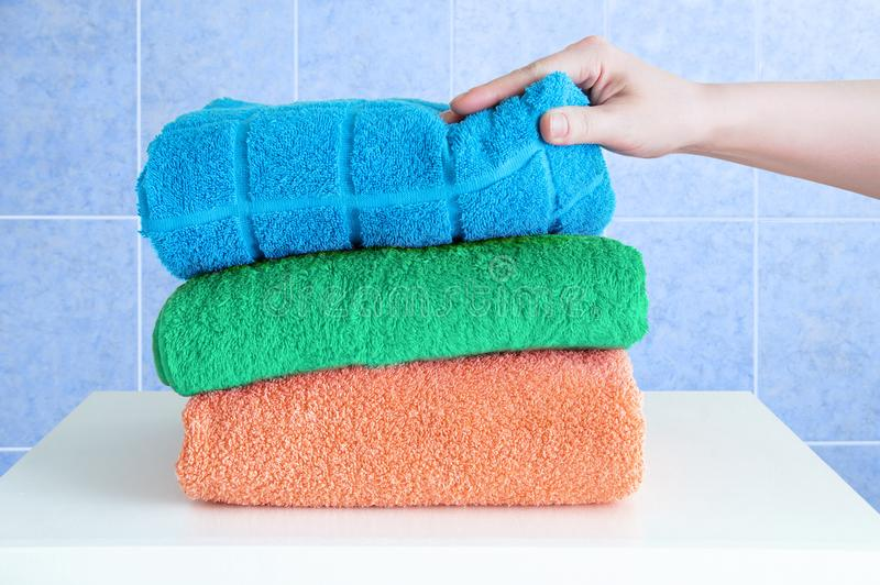 Female hand takes terry towels on a white bedside table in the bathroom. Background blue tile royalty free stock photography