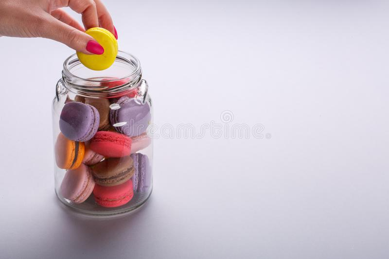 Female hand taking tasty colorful macaroons from glass jar on light gray background. Space for text stock photography