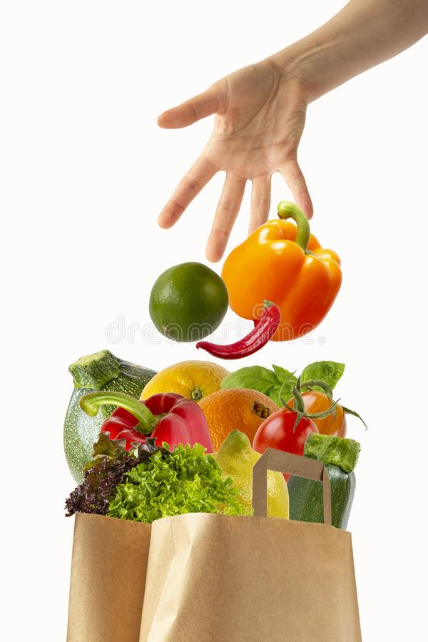 Female hand throwing vegetables in a paper bag with food.Isolated objects on white background. Female hand throwing vegetables in a paper bag with food.Isolated royalty free stock photo