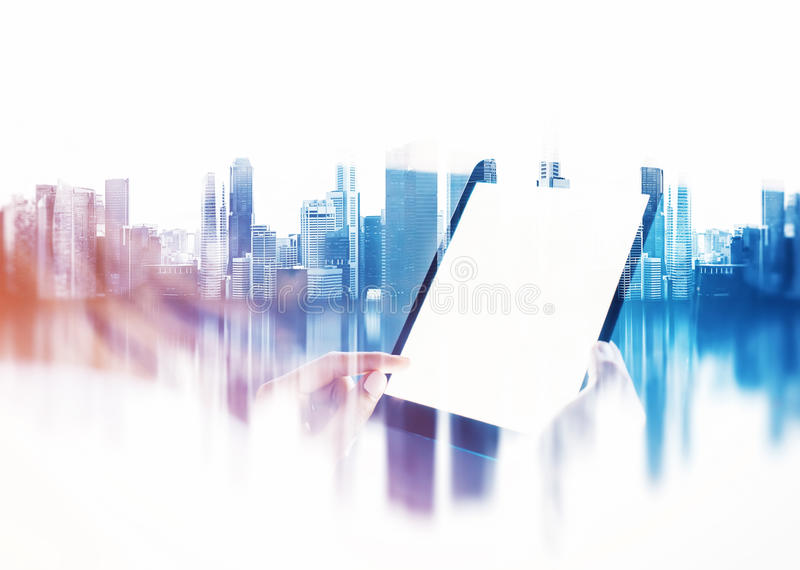 Female hand touching screen of her tablet, blurred city background. Double exposure. Girl touching screen of her tablet on the blurred city background. Double royalty free stock photography