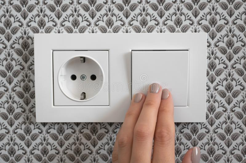 Female hand turn off light switch on plastic switched double socket. Female hand turn off light switch on white plastic switched double socket royalty free stock photos