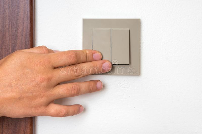 Female hand is turning on or off interior light switch. Female hand is turning on or turning off interior light switch stock image