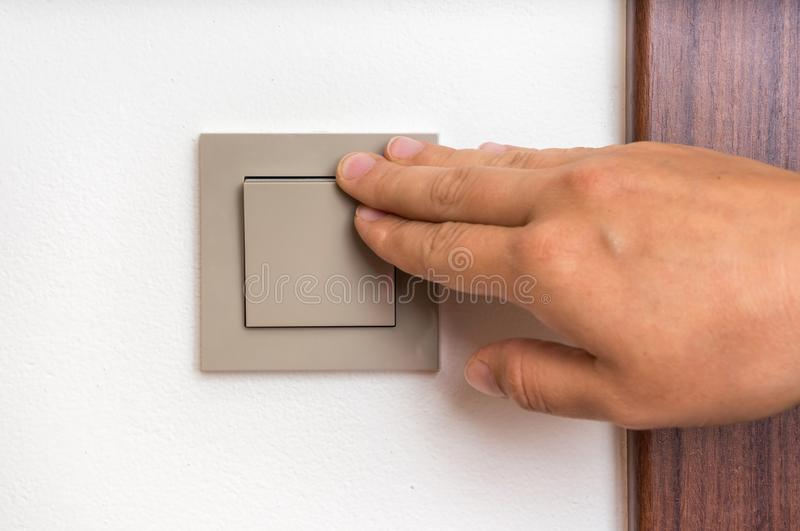 Female hand is turning on or off interior light switch. Female hand is turning on or turning off interior light switch royalty free stock images