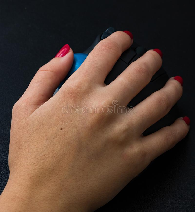Female hand using pc mouse. Close up woman hand on computer mouse on black wooden background royalty free stock images