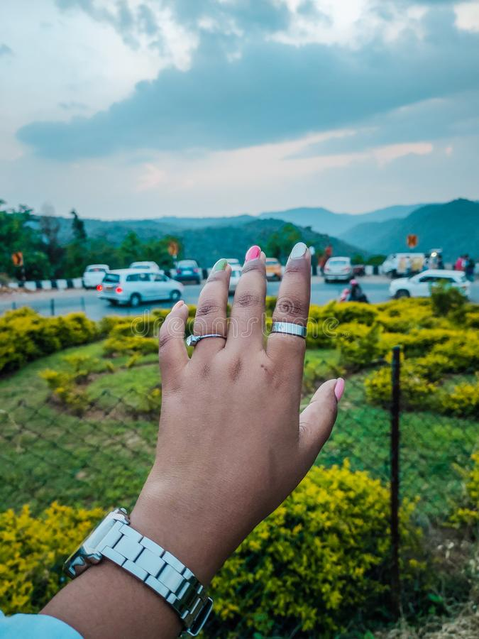 Female hand. Valley view people and mountains in background royalty free stock image