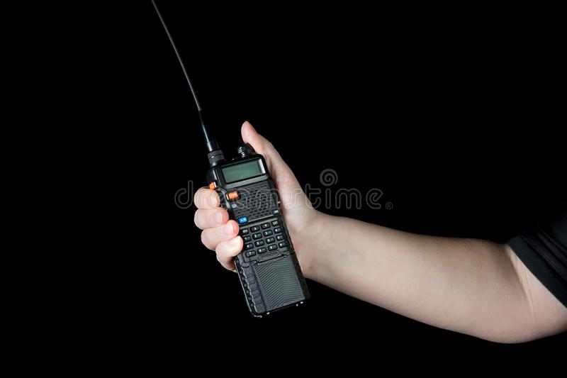 Female hand walkie talkie about the branch isolate. On dark background royalty free stock images
