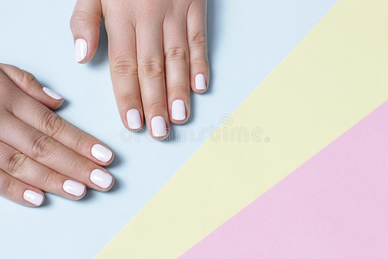 Female hand with white manicure on a knitted background with copy space, top view royalty free stock photography