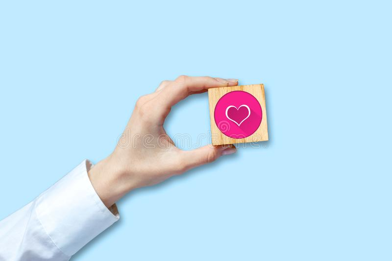 Female hand in a white shirt holds a wooden cube with a social heart icon. Isolated. Love symbol.Social media. Network royalty free illustration