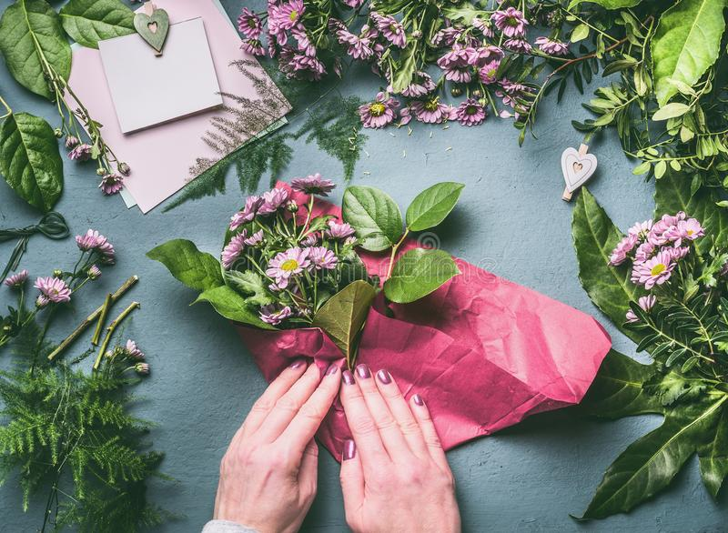 Female hand wrap lovely bouquet of pink flowers in wrapping paper on florist workspace, top view. stock photography
