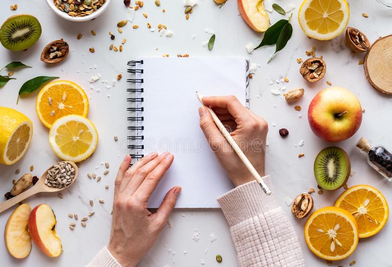 Female hand write in notebook on healthy food background, women diet nutrition royalty free stock photography