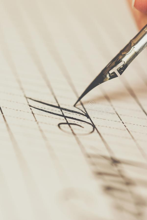 Female hand writes with the inky pen on a white paper sheet with stripes. stationery on desk close up top view. spelling lessons stock photo
