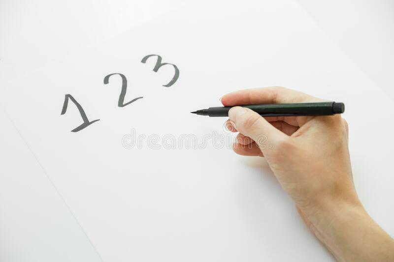 Female hand writing numbers on page stock photos