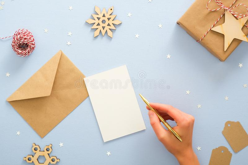 Female hand writing Christmas invitation card mockup over blue background with festive Christmas decorations, confetti, star,. Wooden snowflakes, gift box royalty free stock photos
