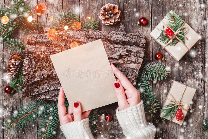 Female hand writing a letter to Santa on wooden background with Christmas gifts, bark texture, Fir branches royalty free stock image