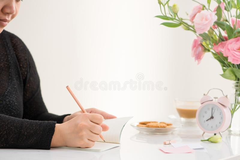 Female hand writing in a notebook at the desk, top view. On the stock images