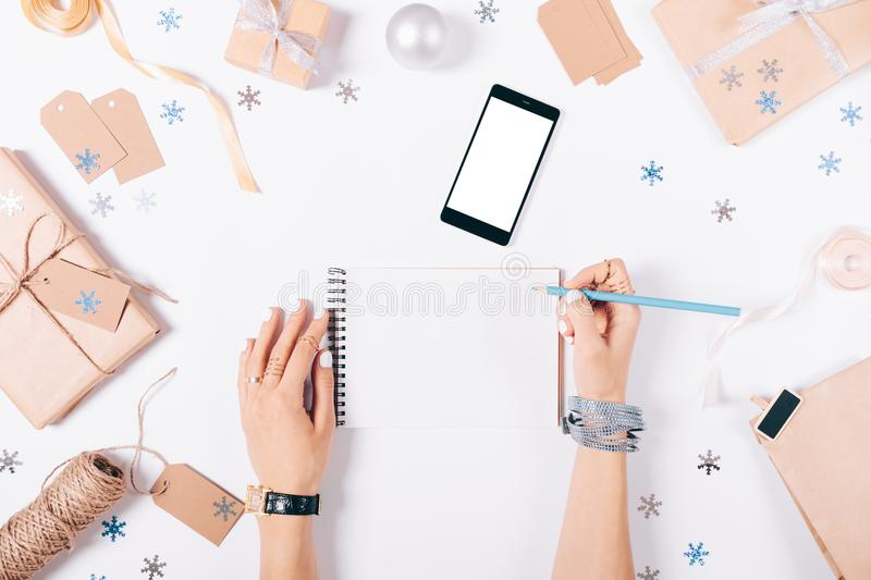 Female hand writing in a notebook shopping list. On white table among the Christmas decorations, top view royalty free stock image