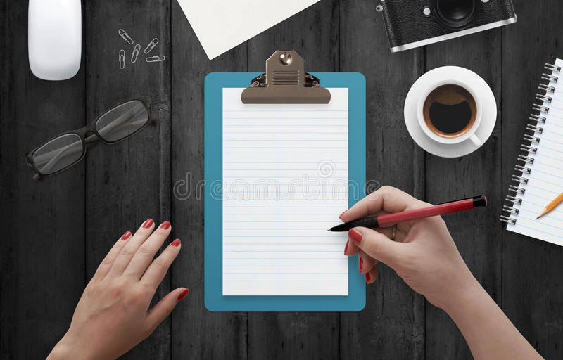 Female hand writing on notebook surrounded with office accessories stock images