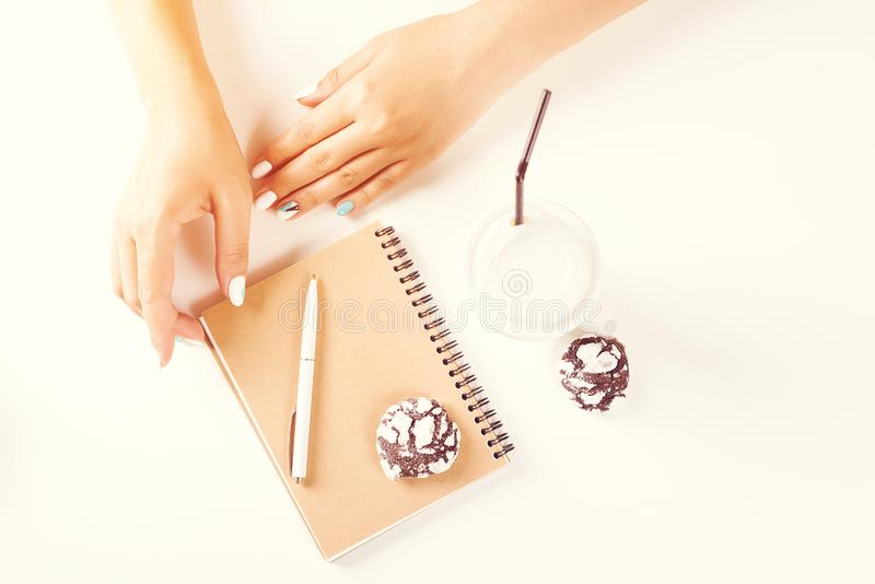 Female hand writing on notebook. Top view of work desk. Coffee, cookies, pencil, notebook. White table. Toned. Morning mood with stock photo