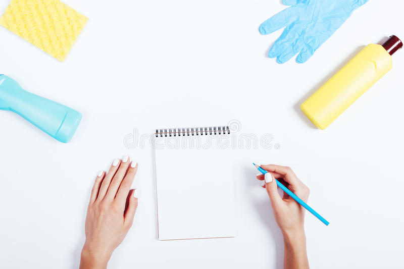 Female hand writing in a notebook, yellow and blue bottle of detergent and a sponge on a white table. Top view stock photo