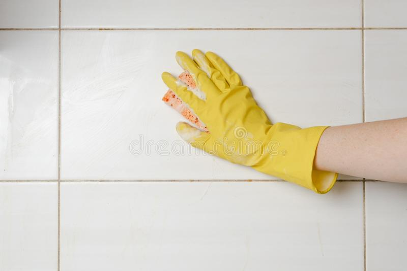 Washing of white tiles with sponge and detergent. Female hand in yellow rubber glove with wisp cleaning wall indoors. Washing of white tiles with sponge and stock images