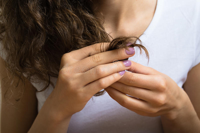 Female hand of a young girl holding the ends of her curly hair. The girl dressed in white t-shirt, her nails purple manicure royalty free stock photography