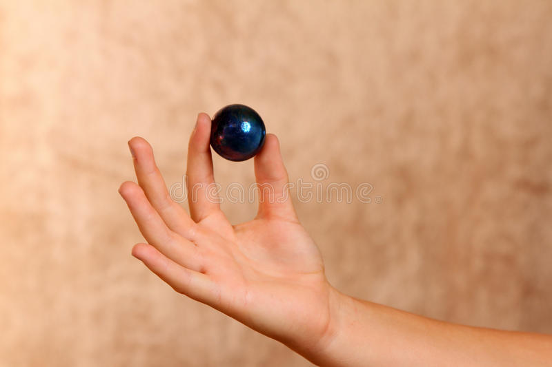 Female Hand. Youth hand Holding Up Blue Sphere stock photography
