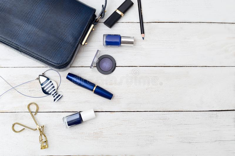 Female handbag of dark blue color and cosmetics on a wooden back. Ground stock image