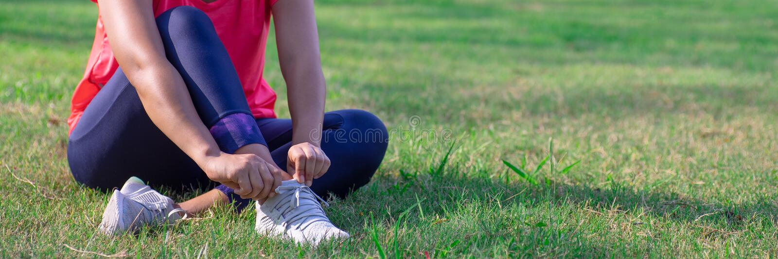 Female hands adjust her running shoes before practice. Runner getting ready for training. Sport active lifestyle concept. Outdoor. Workout concept for web stock images