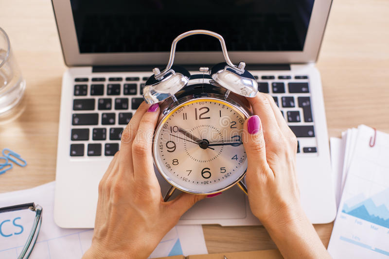 Female hands alarm. Female hands holding alarm clock over desktop with laptop and other items stock photo