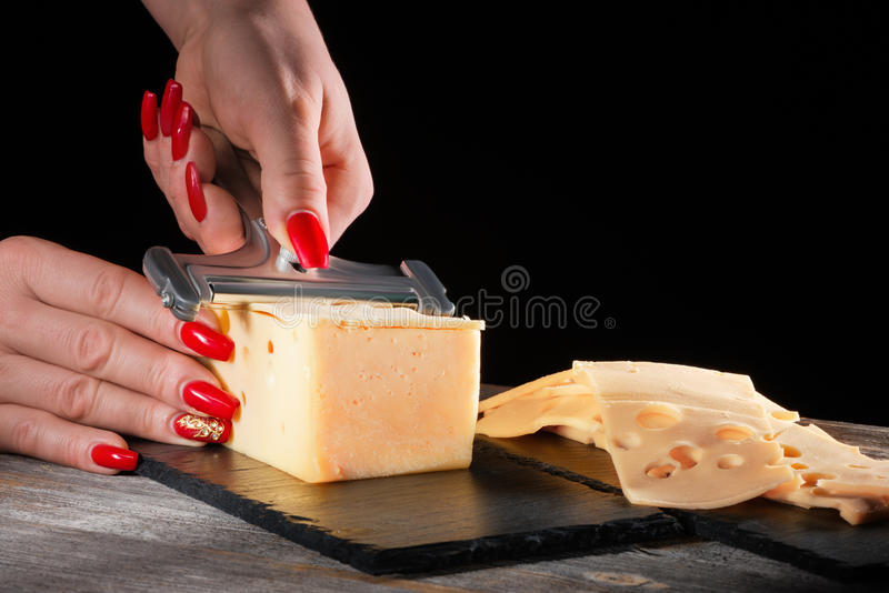 Female hands with beautiful bright manicure cut cheese whetstone by means of a slicer on black slate plate. Female hands with beautiful bright manicure cut stock images