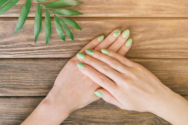 Female hands with summer style green manicure. stock image