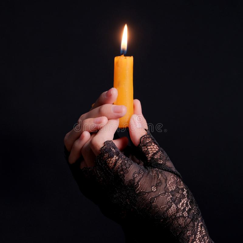 Female hands in black gloves hold a burning candle. Close-up. Black wall background. Square frame. Theme holiday halloween. Mystic royalty free stock photos