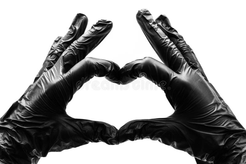 Female hands in black gloves show gestures, signs and symbols  on white background. Two hands fingers folded in the form. Of a heart and love stock image