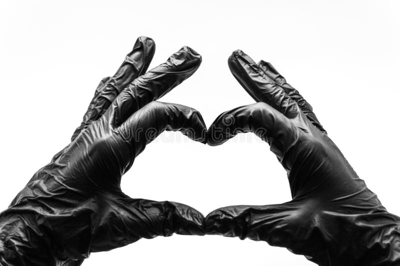 Female hands in black gloves show gestures, signs and symbols isolated on white background. Two hands fingers folded in the form. Of a heart and love stock photos