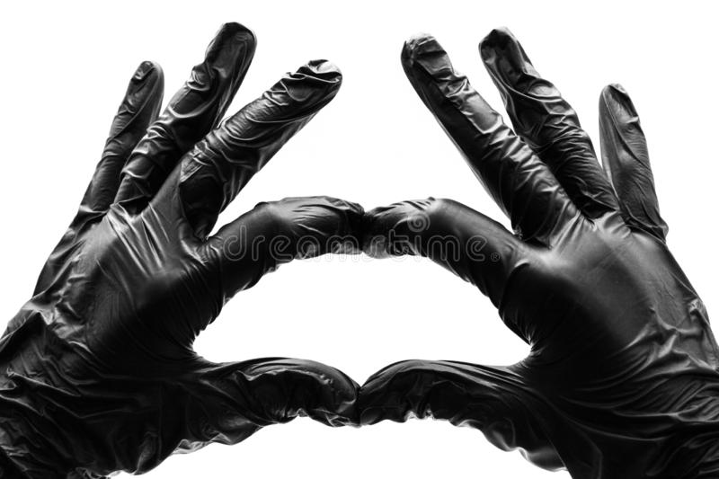 Female hands in black gloves show gestures, signs and symbols isolated on white background. Two hands fingers folded in the form. Of a heart and love royalty free stock image