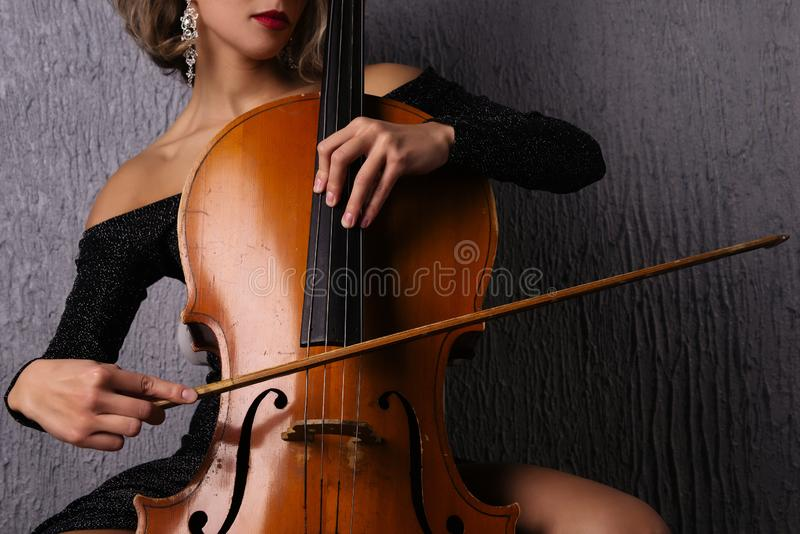 Female hands with a bow on cello strings royalty free stock image