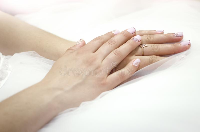 Female hands close-up with wedding ring on finger. Bride in wedding dress royalty free stock photography