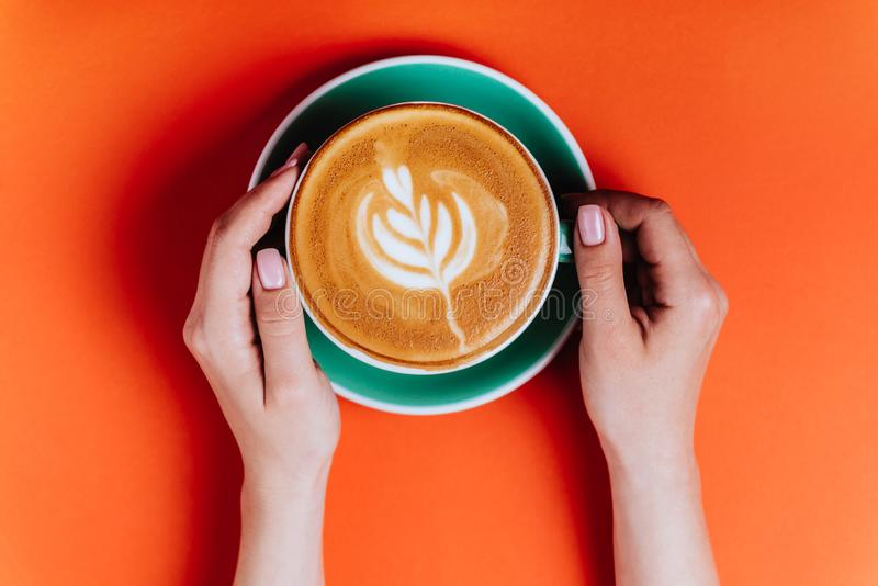 Female hands with a coffee cappuccino cyan cup. Sunny orange toned photo. Warm concept stock photography