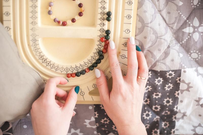 Female hands collect a bracelet from natural stones. A woman or girl and a board for collecting bracelets, necklaces. royalty free stock photo
