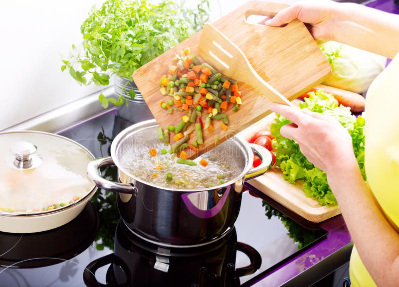 Female hands cooking vegetable soup. In the kitchen royalty free stock photo