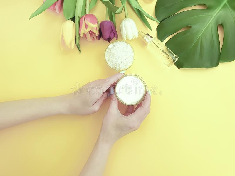Female hands cream cosmetic moisturizing essence flower tulip on a colored background stock image