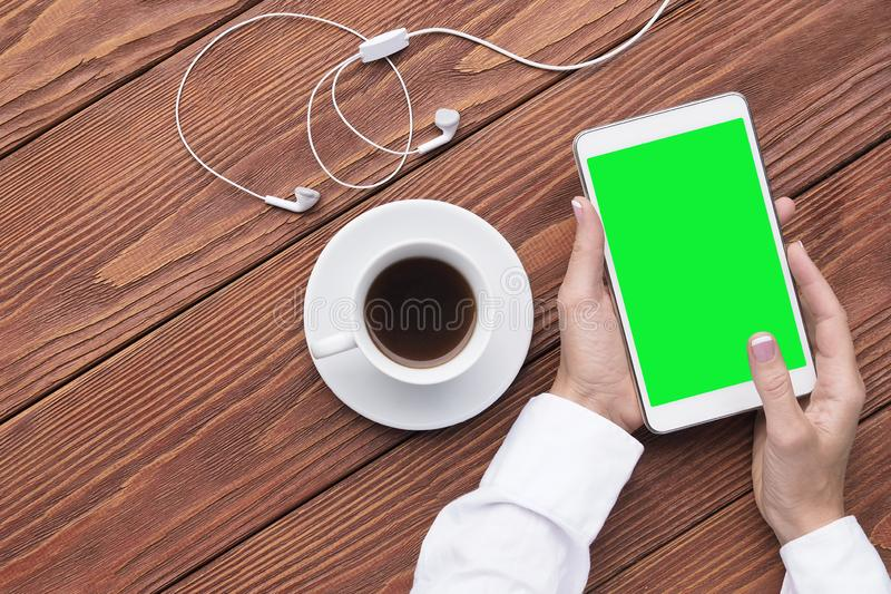 Female hands with cup of coffee and mockup digital tablet and headphones on brown wood desk. Coffee break. Close up, top royalty free stock images