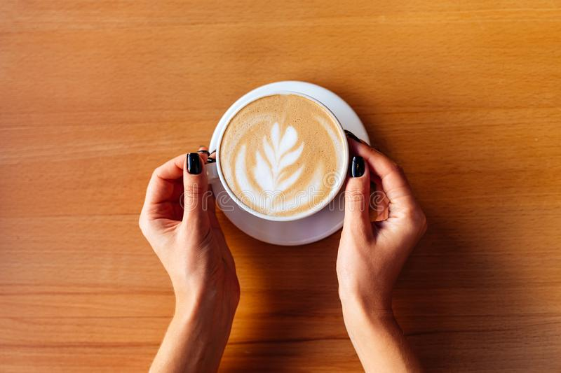 Female hands with cup of hot tasty coffee in cafe stock photography
