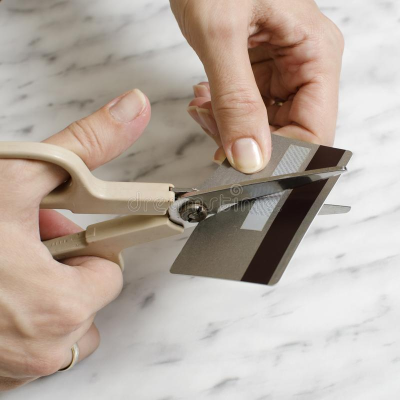Female hands cutting credit card with scissors. Close up royalty free stock image