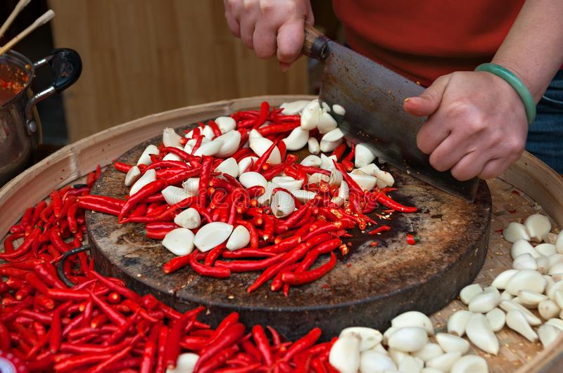 Female hands cutting red chili peppers and garlic royalty free stock photography