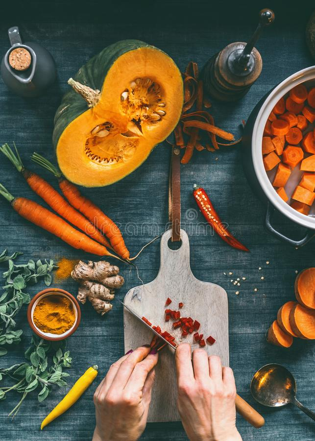 Female hands cutting vegetables for pumpkin soup or vegetarian stew on kitchen table with orange color ingredients. Carrots, sweet potatoes, turmeric and chili stock images