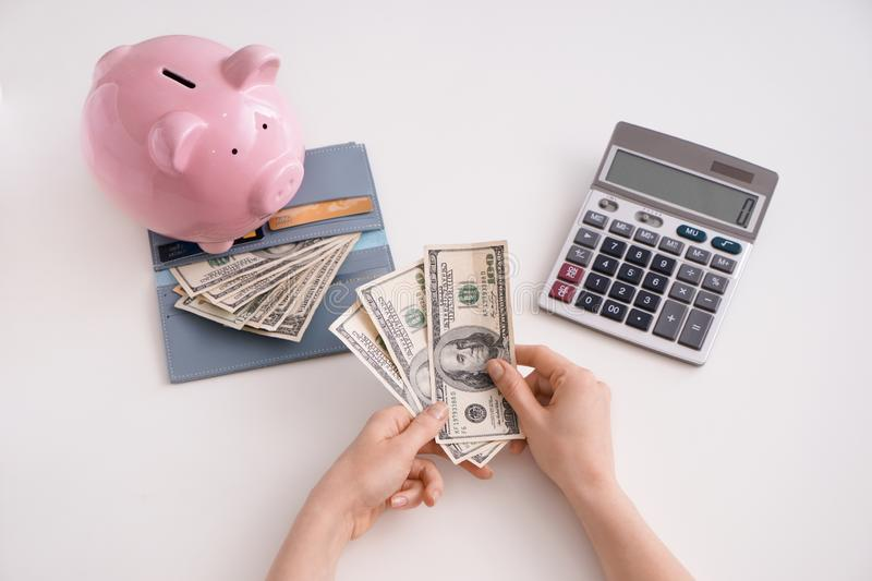 Female hands with dollars, piggy bank, wallet and calculator on white background, top view royalty free stock photos