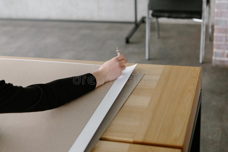 Female hands are drawing on a large wooden table in the loft style in the office royalty free stock photography