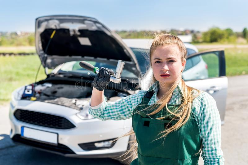 .Beautiful mechanic near car with different tools royalty free stock images
