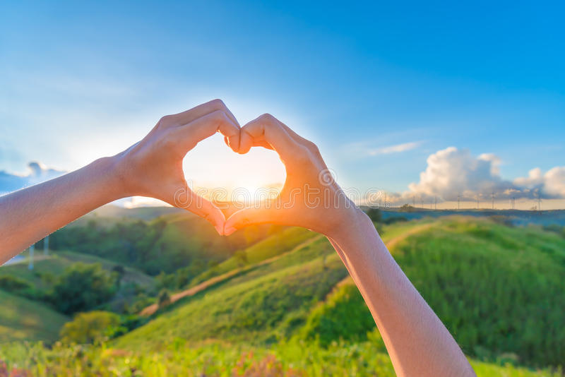 Female hands in the form of heart against sunlight. Behind landscape of windmills plant in blue sky, Hands in shape of love heart - Love green energy stock image